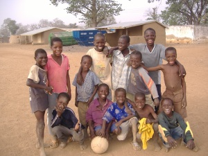 School age boys playing a dusty game of soccer